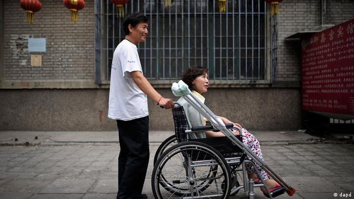 Ni Yulan, in a wheelchair, is helped by her husband Dong Jiqin outside a temporary lodging in Beijing.
