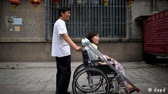 In this photo taken on June 30, 2010, Ni Yulan on a wheelchair is helped by her husband Dong Jiqin outside a temporary lodging in a hotel in Beijing. Ni, a former lawyer and veteran activist left disabled by past police mistreatment, went on trial Thursday, Dec. 29, 2011, the third dissident in a week to be prosecuted as China presses a sweeping crackdown to deter popular uprisings like the ones that shook the Arab world. (AP Photo/Andy Wong)