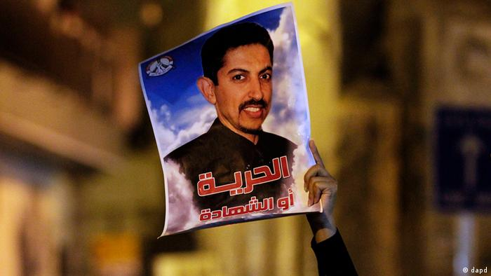 An anti-government protester holds up an image of jailed hunger-striker Abdulhadi al-Khawaja that reads Freedom or martyrdom during a demonstration Sunday, April 8, 2012, in the capital of Manama