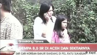 In this image made from Indonesian television TV One, a woman hugging a girl uses a mobile phone shortly after they ran out from a building when a strong earthquake hit in Aceh in Indonesia, Wednesday, April 11, 2012. A tsunami watch was issued for countries across the Indian Ocean after a large earthquake hit waters off Indonesia on Wednesday, triggering widespread panic as residents along coastlines fled to high ground in cars and on the backs of motorcycles. (Foto:TV One via AP Video/AP/dapd) INDONESIA OUT
