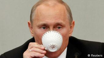 Russia's Prime Minister and President-elect Vladimir Putin drinks from a cup after addressing the parliament at the Russian State Duma in Moscow, April 11, 2012. Several opposition deputies walked out of Russia's lower house of parliament on Wednesday in protest at comments by Prime Minister Vladimir Putin about a dispute over a local election that has triggered a hunger strike. REUTERS/Maxim Shemetov (RUSSIA - Tags: POLITICS)