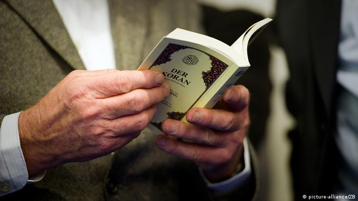 A man holds a copy of the Koran, with the title clearly visible. Taken 08.10.2010 at the book convention in Frankfurt am Main. Foto: Arno Burgi