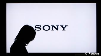 A woman walks past a Sony Corp flat-screen TV at the company's headquarters in Tokyo in this January 22, 2009 file photo. Shares of Sony Corp, the inventor of personal music players, slid more than 7 percent on April 11, 2012 after the company more than doubled its annual loss forecast, highlighting the plight of a Japanese TV industry that once dominated living rooms around the world. To match story SONY/SHARES REUTERS/Toru Hanai/Files (JAPAN - Tags: BUSINESS LOGO)