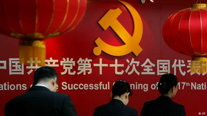 Staff members walk past the communist hammer and sickle emblem at the press center for the 17th National Congress of the Communist Party of China