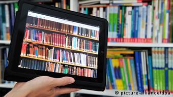 Ein iPad Tablet mit einer Bücherwand auf dem Bildschirm, im Hintergrund ein Bücherregal. Foto: Marc Tirl dpa