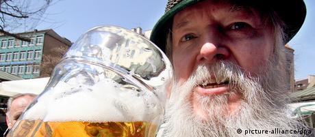Ein Mann in bayerischer Tracht trinkt eine Maß Bier.