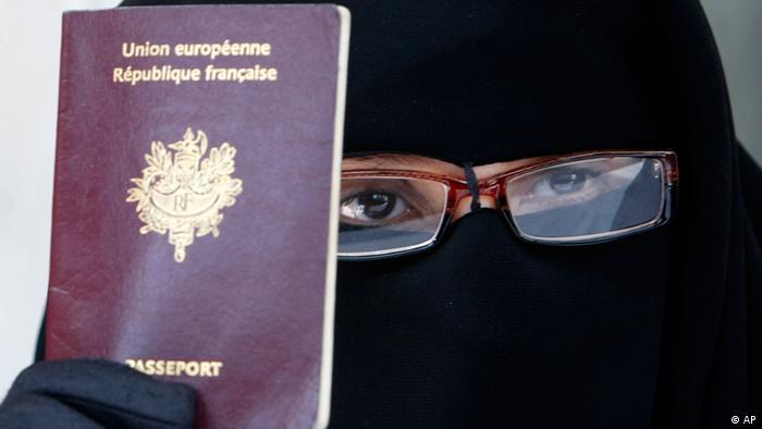 Женщина в никабе держит в руке французский паспорт