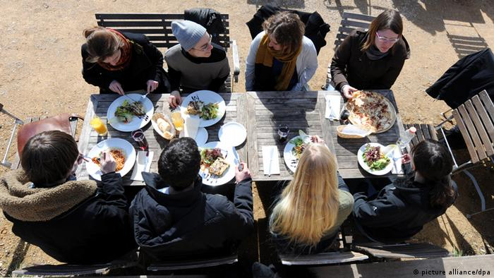 Studenten sitzen in einem Café und essen zu Mittag