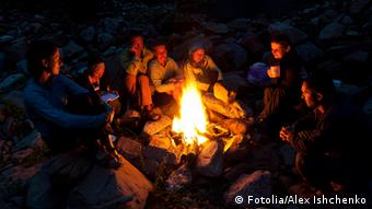 Group of backpackers relaxing near campfire