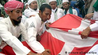 Indonesian Muslims destroy a Danish flag during demonstration outside Danish embassy February 2006.