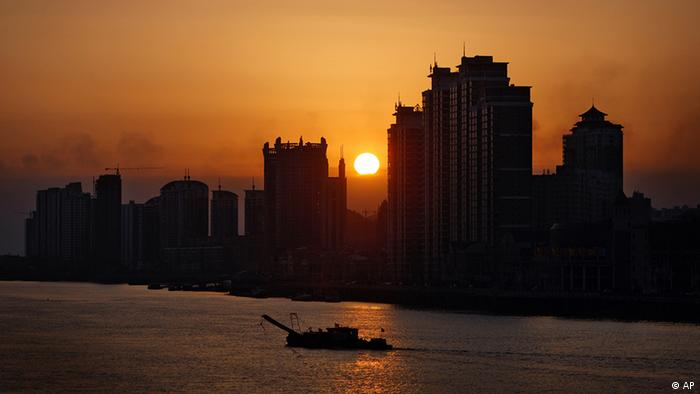 A Chinese boat sails past office and residential buildings at the sunset on the Yalu River
