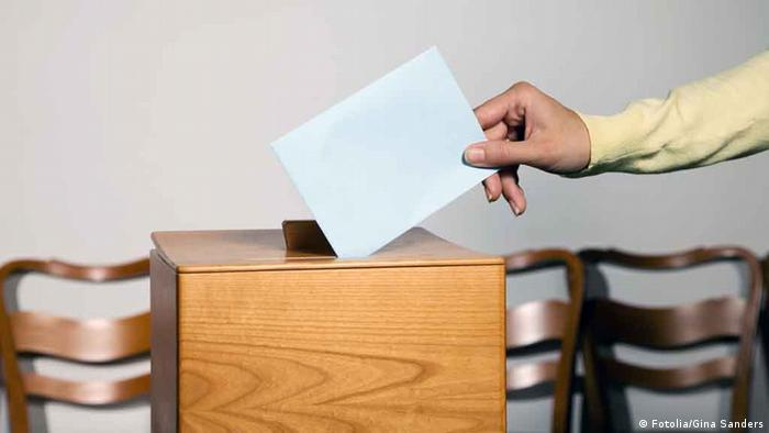 A person putting a ballot into a ballot box