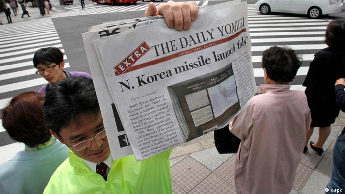 A newspaper employee shows an extra issue of the Daily Yomiuri reporting North Korea's rocket launch to hand over to passers-by in Tokyo, Japan, Friday, April 13, 2012. North Korea fired a long-range rocket early Friday, South Korean and U.S. officials said, defying international warnings against moving forward with a launch widely seen as a provocation.(Foto:Itsuo Inouye/AP/dapd)