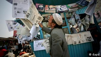 An Afghan man looks at a newspaper