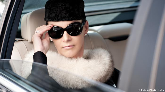 Wealthy-looking woman sitting in a car with sunglasses on