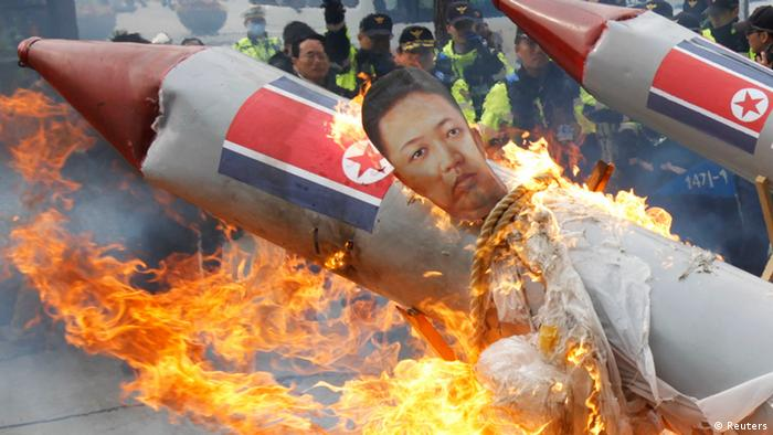 Protesters, from conservative, right-wing and anti-North Korean civic groups, burn an effigy of North Korean leader Kim Jong-Un bound on a mock North Korean missile during a protest against the North's rocket launch