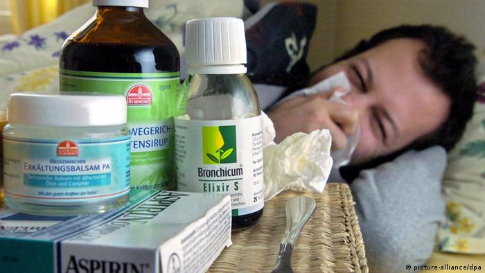 A man lying in bed with a lot of flu medication. (Photo: Patrick Lux/dpa/lno)