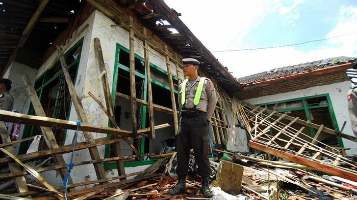 Indonesien Gewalt Ahmadiyah Muslime Polizist vor zerstörtes Haus
