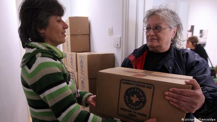 Antigoni (L), a volunteer, hands over a packet with food to a woman in need at the NGO Doctors of the World (Medecins du Monde) in Perama EPA/ORESTIS PANAGIOTOU