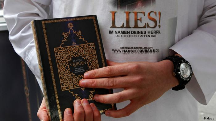 A man holding a copy of the Koran