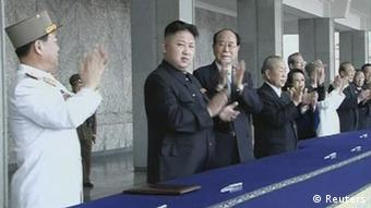 Kim Jong-un (center) applauding the parde in Pyongyang from a viewing stand