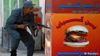 An Afghan policeman takes position at the site of an attack in Kabul April 15, 2012