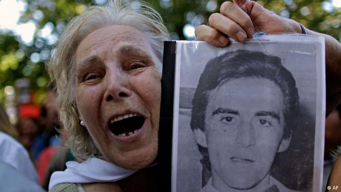 Pepa Pussek holds a picture of her son Juan Carlos Galvan, one of the victims killed during Argentina's dirty war, as she listens to the sentence for former dictator Jorge Videla in Cordoba, Argentina, Wednesday Dec. 22, 2010. Videla was sentenced to life in prison Wednesday for the torture and murder of 31 prisoners in 1976. It was the first conviction for the military junta leader, who led the military coup that installed Argentina's 1976-1983 dictatorship, in 25 years of democracy. (AP Photo/Natacha Pisarenko)