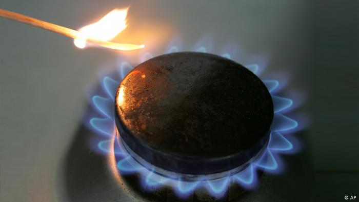 A gas hob on an oven, alight, with a lit match next to it. (AP Photo/Joerg Sarbach)
