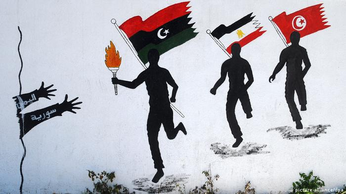 Arab flags held by figures running, with Libya first, Egypt second and Tunisia third. Two outstretched hands, representing Syria and Yemen