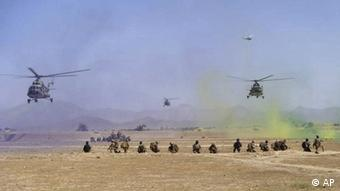 Two helicopters providing cover to soldiers in the field