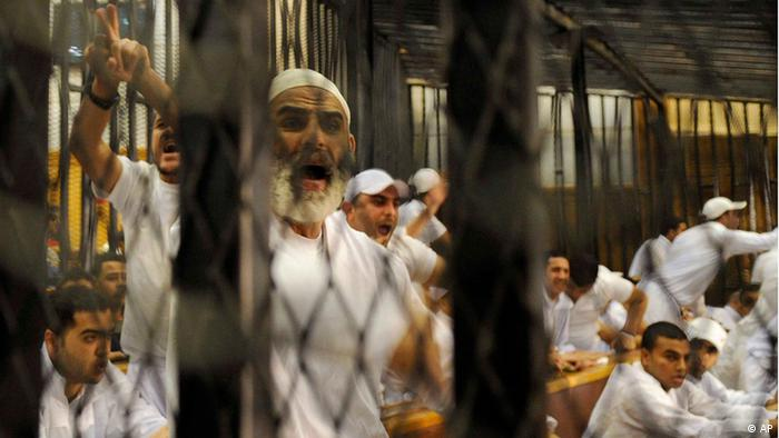 Egyptian defendants who face charges relating to the deaths after a soccer match in the Mediterranean city of Port Said Feb. 1, 2012, chant slogans inside a cage during their trial at a court house in Cairo