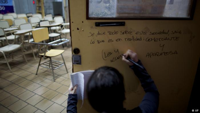 A student writes a slogan on the door of a classroom in an occupied university in Buenos Aires, Argentina