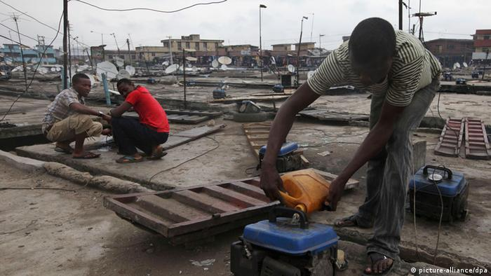A man refuels a small generator in Lagos