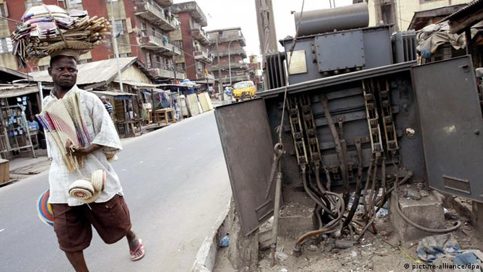 A man walks past a damaged transformer in Lagos, Nigeria.