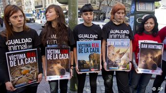 Animal rights protesters hold placards near a hospital in Madrid Tuesday April 17, 2012 where King Juan Carlos was being treated.
