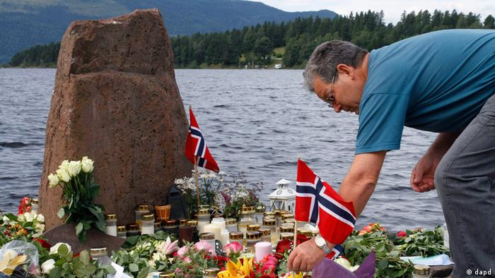 A man places a Norwegian flag between flowers in Utvika in front of the Utoya island, near Oslo, Norway, Tuesday, July 26, 2011, where a gunman Anders Behring Breivik killed at least 76 people. The defense lawyer for Anders Behring Breivik said Tuesday his client's case suggests he is insane, adding that someone has to take the job of defending him but that he will not take instructions from his client. Geir Lippestad told reporters that the suspect in the bombing on the capital and the brutal attack on a youth camp that killed at least 76 people is not aware of the death toll or of the public's response to the massacre that has rocked the country. (Foto:AP/dapd)