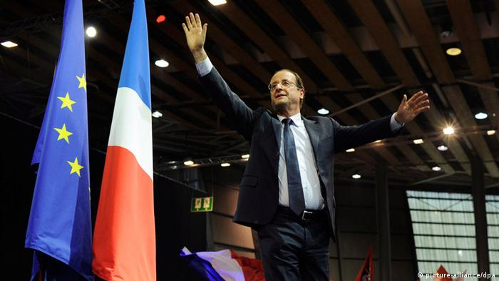 Francois Hollande waves at the audience before making a speech during a campaign meeting in Lille