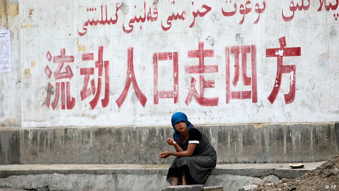 Eine uigurische Frau sitzt vor einer Wand auf dem der Slogan Volk, ziehe in alle Richtungen steht (Foto: AP)