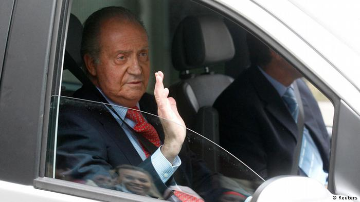 Spain's King Juan Carlos waves from inside a car as he leaves a hospital after being discharged in Madrid April 18, 2012. King Juan Carlos came under intense media fire on Sunday for hunting elephants in Botswana when his country was being sucked back into the euro zone's financial crisis and one young Spaniard out of two was unemployed. The royal holiday last week would have remained secret if the king had not tripped on a step, fractured his hip and had to be flown back urgently to Madrid to undergo hip replacement surgery on Saturday morning. REUTERS/Andrea Comas (SPAIN - Tags: ROYALS HEALTH POLITICS ENTERTAINMENT)