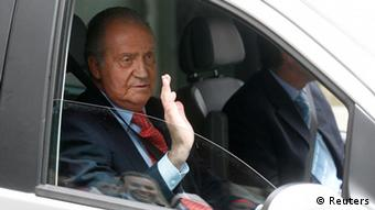 Spain's King Juan Carlos waves from inside a car as he leaves a hospital after being discharged in Madrid April 18, 2012.
