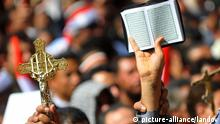 Image #: 13543334 Egyptian protesters holds a Christian cross and the Koran, Islam's holy book, while others shout slogans at Cairo's Tahrir Square on March 11, 2011 as hundreds of Egyptians demonstrated against sectarianism, following religious clashes that left at least 13 people dead. UPI/Mohammed Hosam /LANDOV