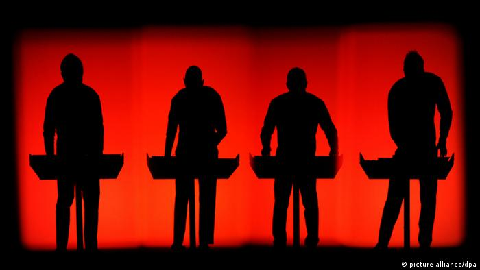 Kraftwerk on stage in front of a red background Copyright: Peter Steffen/dpa