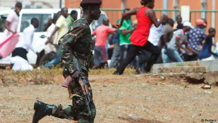 A soldier disperses a group of demonstrators