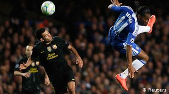 Didier Drogba (R) of Chelsea and Sergio Busquets of Barcelona jump for a header during their Champions League semi-final first leg soccer match at Stamford Bridge in London April 18, 2012. REUTERS/Albert Gea (BRITAIN - Tags: SPORT SOCCER TPX IMAGES OF THE DAY)