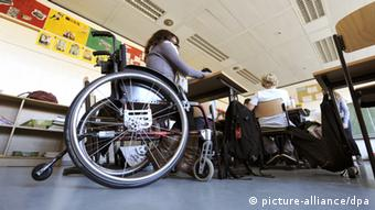 A student in a wheelchair sits in a classroom with other students
