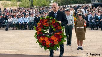 President Peres lays a wreathat Yad Vashem watched by many seated participants, many in uniform.
