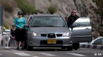 Israelis stand still next to their cars on a highway as a two-minute siren sounds