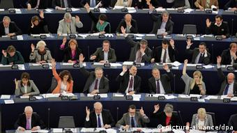 EU politicians voting on EU passenger data, either raising their hands Yes or keeping them down, No. (Photo: REUTERS/Vincent Kessler)