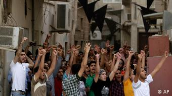 Bahraini anti-government protesters chant slogans toward riot police in Manama, Bahrain, Thursday, April 19, 2012. Nervous shop owners closed their doors and security forces fanned out across Bahrain's capital Thursday in attempts to quell widening unrest that threatened to overshadow the return of the Formula One Grand Prix to the Gulf kingdom. (Foto:Hasan Jamali/AP/dapd)
