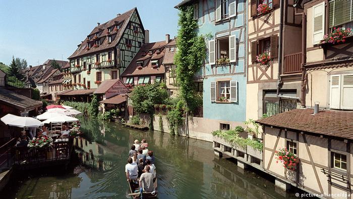 Touristen befahren mit einem Boot einen Kanal in einer mittelalterlichen Stadt.